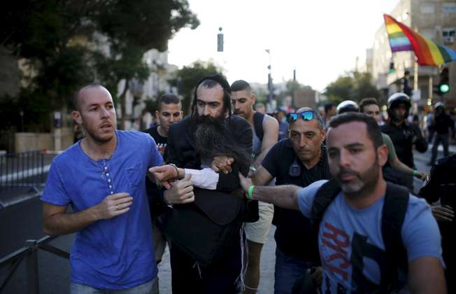 People detain after disarming an Orthodox Jewish assailant, after he stabbed and injured six participants of an annual gay pride parade in Jerusalem on Thursday, police and witnesses said July 30, 2015. (REUTERS/Amir Cohen)