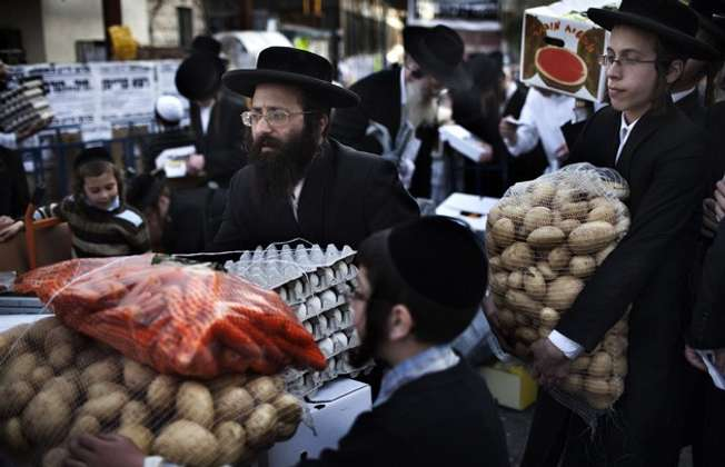 Ultra-Orthodox Jews in Jerusalem carry donated food for the poor from a food distribution center before the Passover holiday, (AFP)