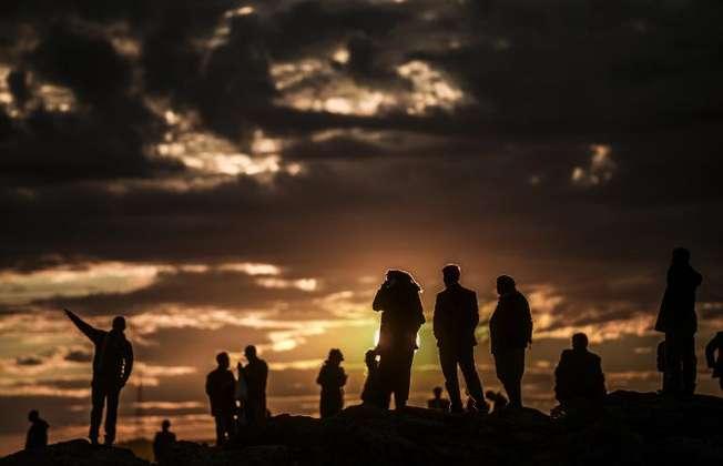 Kurdish people watch the Syrian town of Kobane at sunset from the Turkish village of Mursitpinar on October 19, 2014 (Bulent Kilic (AFP))