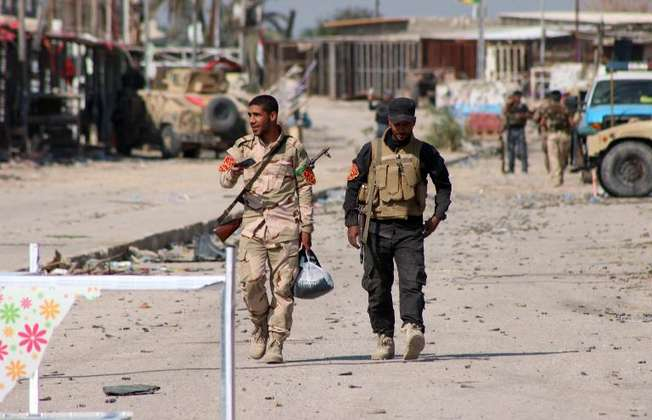 Iraqi soldiers walk in Jurf al-Sakhr on October 27, 2014 after military forces retook the large area south of the capital from Islamic State group militants (Haidar Mohammed Ali (AFP))