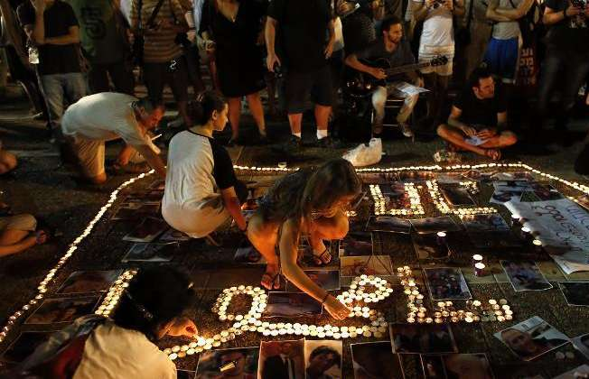 Israelis light up candles near pictures as thousands of supporters of peace gather at the Rabin Square in Tel Aviv on July 26, 2014 (Thomas Coex (AFP))