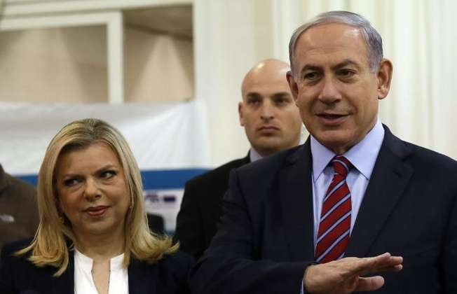 Israeli Prime Minister Benjamin Netanyahu stands next to his wife Sara as he speaks to the media in Jerusalem, on December 31, 2014 (Gali Tibbon (AFP))