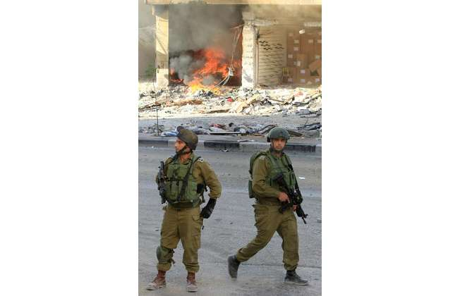 Israeli military members walk past a burning shop during an operation in the southern West Bank city of Hebron on September 23, 2014 (Hazem Bader (AFP))