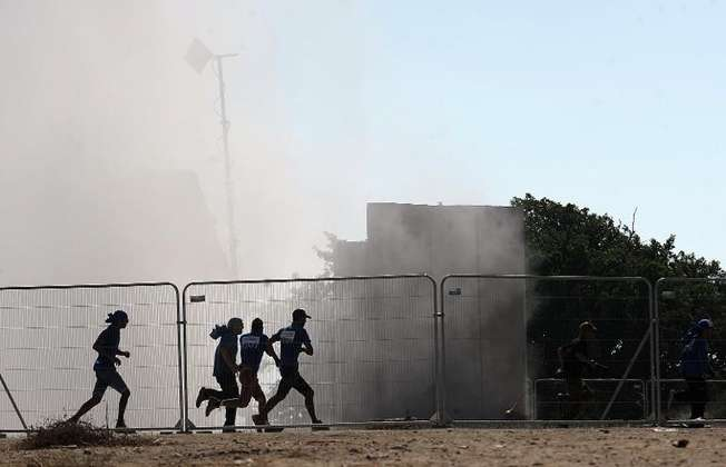 Israelis run for cover seconds after an Iron Dome system (background) fired an anti-rocket missile near the city of Ashkelon on August 26, 2014 (David Buimovitch (AFP))