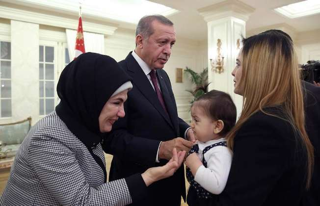 A photo released on September 21, 2014 by the Turkish presidential press office shows President Recep Tayyio Erdogan (C) and his wife Emine (L) greeting some of the freed Turkish consulate hostages at the Cankaya Presidential Palace in Ankara (Kayhan Ozer (Presidential Press Office/AFP/File))