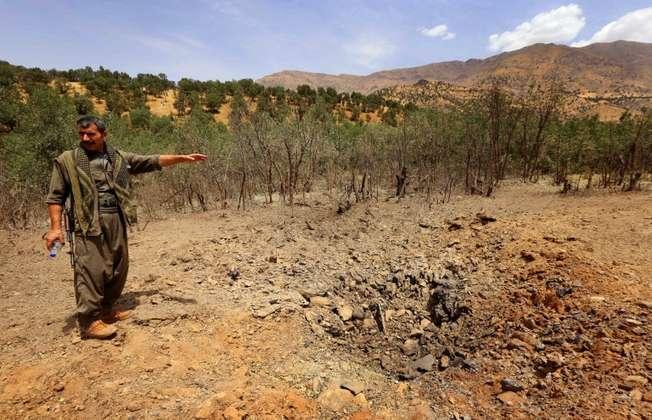 مقاتل من حزب العمال الكردستاني يشير الى حفرة احدثتها غارة تركية على جبال قنديل (سافين حميد (اف ب))