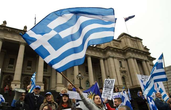 """Protesters wave the Greek flag as they shout """"Oxi"""" (No) during the """"Melbourne stands with Greece"""" solidarity rally outside Parliament House in Melbourne on July 4, 2015 (Theo Karanikos (AFP))"""