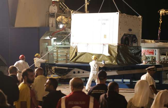 "A container with the bodies of migrants is unloaded from the Swedish coast guard ship ""Poseidon"" in the port of Palermo on August 27, 2015 (Marcello Paternostro (AFP))"