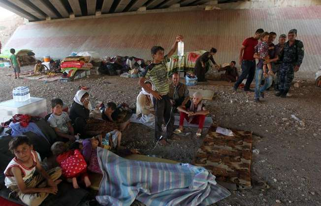 Iraqi Yazidis, who fled their homes a week ago when Islamic State militants attacked the town of Sinjar, gather at a makeshift shelter on August 10, 2014 in the Kurdish city of Dohuk (Ahmad al-Rubaye (AFP))