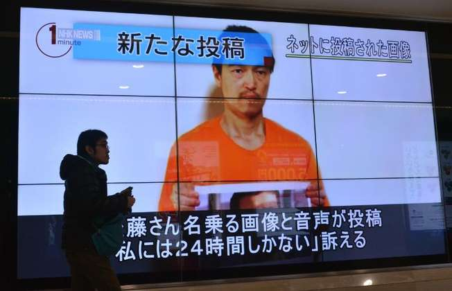 A pedestrian looks at a large screen in Tokyo, Japan, on January 28, 2015, showing television news reports about hostage Kenji Goto who has been kidnapped by the Islamic State group (Kazuhiro Nogi (AFP))