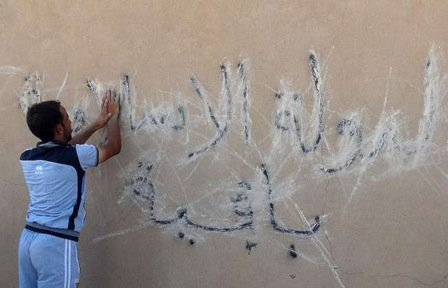 "An Iraqi man scribbles over graffiti on the wall reading in Arabic, ""the Islamic State (group) is staying"" in Barwanah on September 10, 2014 ( Azhar Shallal (AFP/File) )"