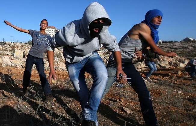 Un manifestant palestinien jette une pierre sur les forces de sécurité israélienne près du village de Silwad, en Cisjordanie, le 26 septembre 2014 (Abbas Momani (AFP))
