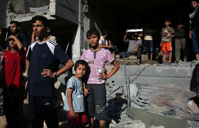 Palestinians gather around the rubble of a building destroyed following an Israeli military strike in Rafah, southern Gaza on August 21, 2014 (Said Khatib (AFP))