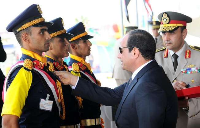 Abdel Fattah al-Sisi (right) honours a recruit during a graduation ceremony of the Technical Institute for the Egyptian armed forces in Cairo on June 21, 2014 (Egyptian Presidency/AFP)