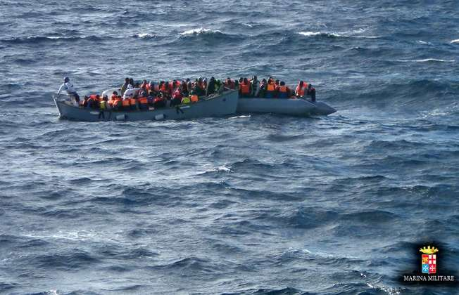 Migrants sit in a boat during a rescue operation off the coast of Sicily in 2014 ( - (Marina Militare Italiana/AFP/File) )