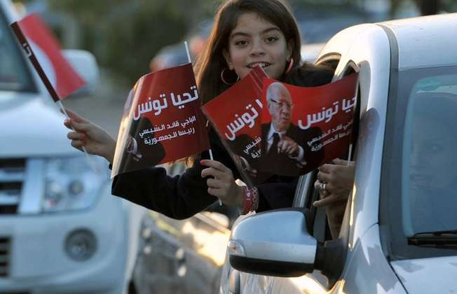 A young girl holds flags from a car as supporters of newly-elected President Beji Caid Essebsi celebrate his victory on December 22, 2014 in Tunis (Fethi Belaid (AFP))