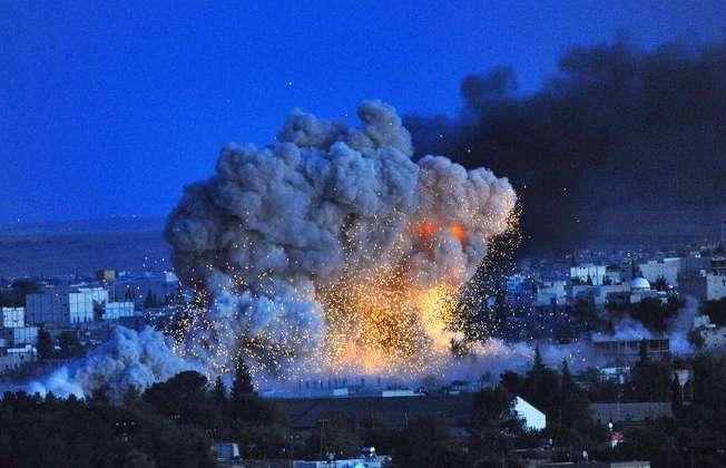 Explosion dans la ville syrienne de Kobané défendue par les Kurdes, photographiée depuis le village turc de Mursitpinar le 20 octobre 2014 (Bulent Kilic (AFP))