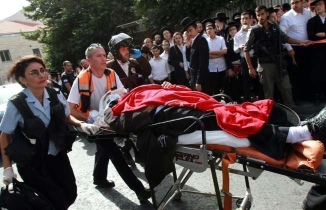 Des forces de sécurité et des secouristes transportent un Israélien blessé après une attaque à la voiture bélier et au couteau à un arrêt de bus à Jérusalem le 13 octobre 2015 (GIL COHEN MAGEN (AFP))