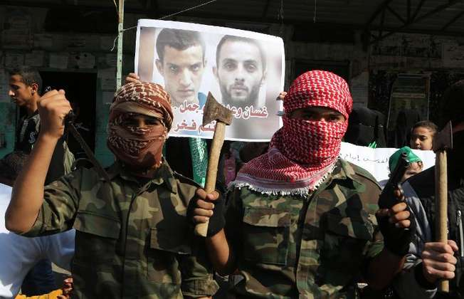 Masked Palestinians hold knifes and axes as they celebrate an attack on a Jerusalem synagogue, in front of a poster of attackers Ghassan and Uday Abu Jamal, during a rally in Rafah in the southern Gaza Strip on November 18, 2014 (Said Khatib (AFP))