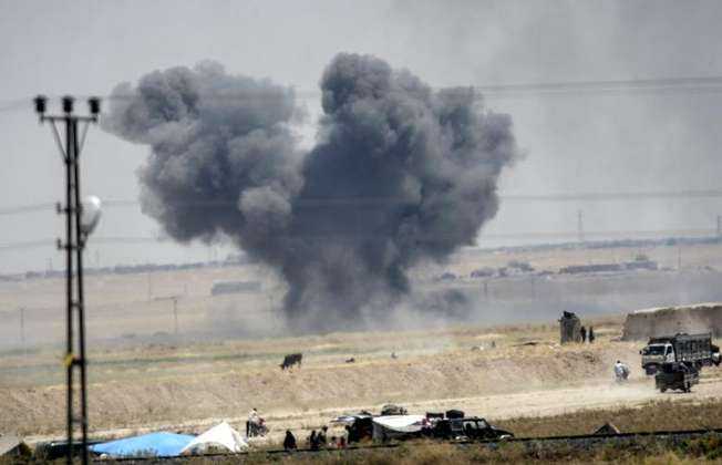 Black smoke billows into the sky after an airstrike during clashes in the eastern part of Tal Abyad on June 14, 2015 (Bulent Kilic (AFP))