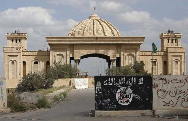 A general view taken on April 5, 2015 shows a defaced Islamic State group flag in front of the main gate of the palace of former Iraqi dictator Saddam Hussein in Tikrit after Iraqi forces retook the northern city from Islamist jihadists (Mohammed Sawaf (AFP/File))