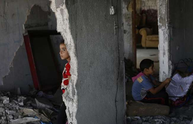 Palestinian children from the Msabeh family gather at their family home which was destroyed during the 50-day war between Israel and Hamas in July and August, in the Shejaiya neighborhood of Gaza City, on October 9, 2014 (Mohammed Abed (AFP))