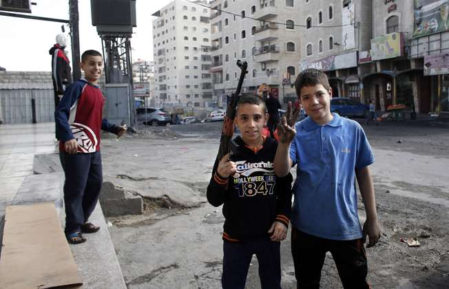 Palestinian boys with a toy gun in East Jerusalem neighborhood of Shuafat (AFP/Thomas Coex)