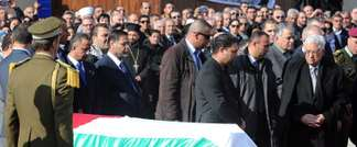Palestinian president Mahmoud Abbas (right) stands by the coffin during the funeral of Ziad Abu Ein in Ramallah on December 11, 2014 (Abbas Momani (AFP))