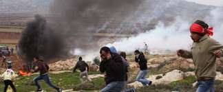 Palestinian protesters take cover from tear gas thrown by Israeli security forces during clashes following a demonstration against Israeli settlements in the West Bank village of Turmus Aya, north of Ramallah on December 19, 2014 (Abbas Momani (AFP))