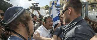 Israeli policemen scuffle with right-wing Israelis who were trying to jump a barrier to cross into the al-Aqsa mosque compound in the old city of Jerusalem, on October 30, 2014 after Israeli authorities temporarily closed the compound (Jack Guez (AFP))