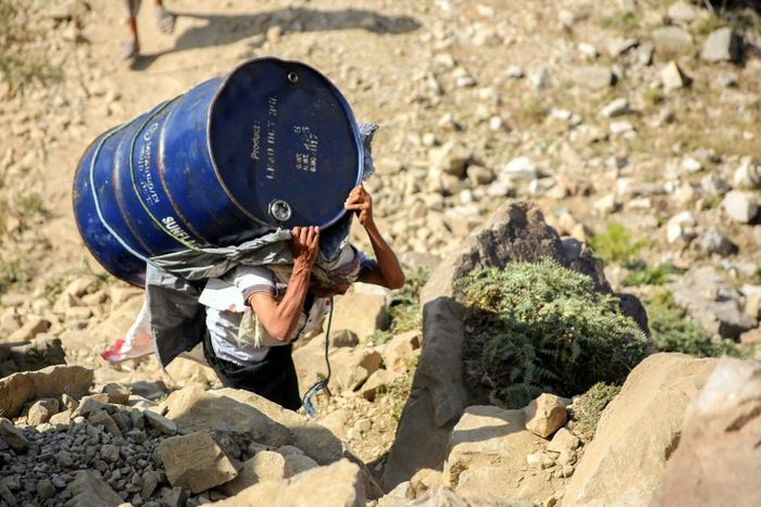 A Yemeni man carries a barrel of supplies as he walks through the mountains along the only path accessible between the southern cities of Aden and Taez on December 26, 2015. AFP PHOTO / AHMAD AL-BASHA