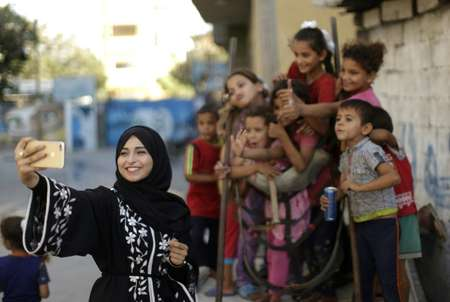 Palestinian Fatma Mosabah, 21, says she takes pictures with anyone in a bid to show a different side of life in Gaza, sometimes at the cost of antagonising conservatives ( MAHMUD HAMS (AFP) )