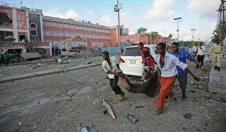 People carry a body after the explosion near the Sahafi hotel in Mogadishu ( Mohamed Abdiwahab (AFP) )