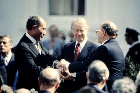 On March 26, 1979, then US president Jimmy Carter (C) congratulates Egyptian president Anwar Sadat (L) and Israeli premier Menachem Begin (R) in a three-way handshake on the north lawn of the White House, after signing the Camp David Accords ( - (CONSOLIDATED NEWS PICTURES/AFP/File) )
