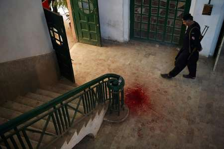 A Pakistani policeman looks at the blood-stained floor of the Agriculture Training Institute following an attack by Taliban militants in Peshawar on December 1, 2017 ( ABDUL MAJEED (AFP) )