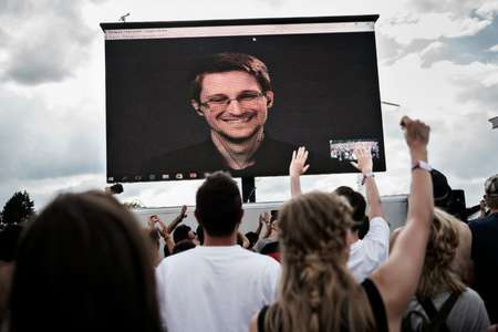 NSA whistleblower Edward Snowden is seen on a giant screen as he is interviewed by performance group The Yes Men live at the Roskilde Festival in Denmark on June 28, 2016 ( Mathias Loevgreen Bojesen (Scanpix/AFP/File) )