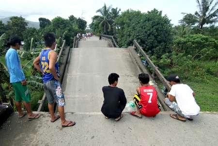 فيليبينيون يتفقدون جسرا تضرر جراء الزلزال في سوريغاو في 11 شباط/فبراير 2017 ( اروين ماسكاريناس (اف ب) )