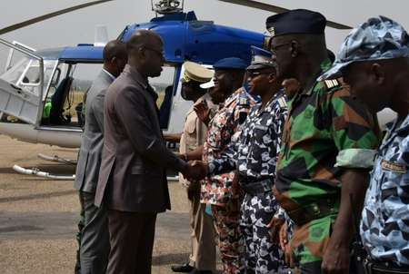 Ivory Coast Defence Minister Alain-Richard Donwahi (L) shakes hands with military commanders upon his arrival at the airport in Bouake ( Sia KAMBOU (AFP) )