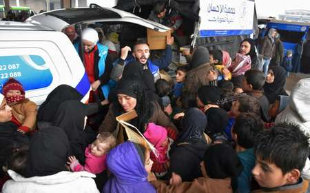 Syrians who fled from rebel-held areas in east Aleppo receive aid food on December 1, 2016, at a warehouse in a small village on the city's  eastern outskirts ( George Ourfalian (AFP) )