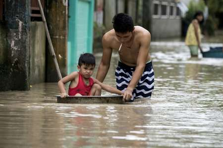 Un père pousse son fils dans une bassine dans une rue inondée par le typhon Mangkhut à Bulacan, aux Philippines, le 16 septembre 2018. ( NOEL CELIS (AFP) )