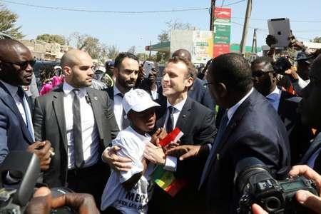 الرئيس الفرنسي ايمانويل ماكرون يعانق ولدا خلال زيارة الى مدرسة ثانوية في دكار في 2 شباط/فبراير 2018. ( لودفيك ماران (AFP) )