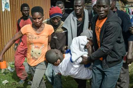 People carry the body of a man allegedly shot dead by police in Friday's clashes ( SIMON MAINA (AFP) )