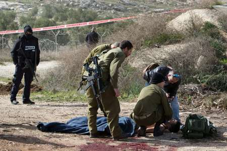 An injured Palestinian suspected attacker is treated by Israeli medic soldiers after he was shot following a stabbing attack on January 18, 2016 in the Tekoa settlement, south of Jerusalem ( Menahem Kahana (AFP) )