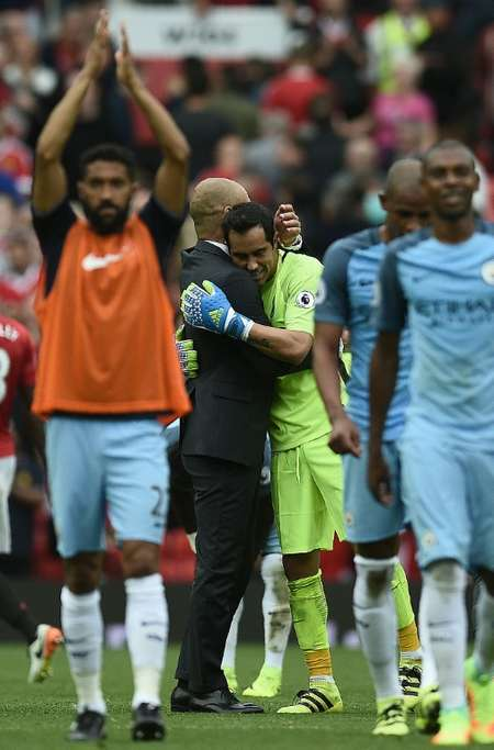 Manchester City's manager Pep Guardiola embraces goalkeeper Claudio Bravo as they celebrate after defeating Manchester United in their English Premier League match, at Old Trafford, on September 10, 2016 ( Oli Scarff (AFP) )