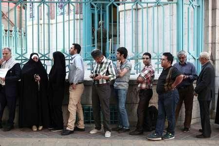 Des Iraniens patientent à l'ouverture d'un bureau de vote à Téhéran, le 19 mai 2017, jour d'élection présidentielle ( Behrouz MEHRI (AFP) )