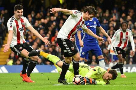 Chelsea's goalkeeper Asmir Begovic gets his gloves on the ball to stop Brentford's Lasse Vibe (C) from scoring during their English FA Cup fourth round football match in London on January 28, 2017 ( Glyn KIRK                           (AFP) )
