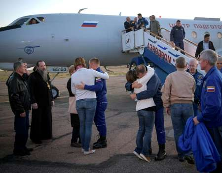 Aleksey Ovchinin, centre, and Nick Hague, right, embrace their families after landing ( Bill INGALLS ((NASA/Bill Ingalls)/AFP) )