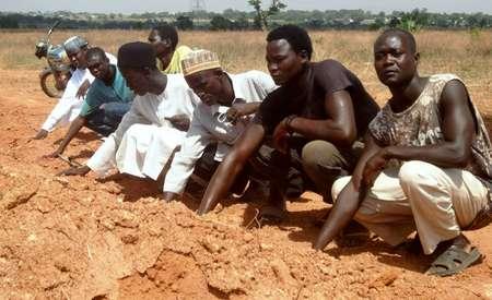 Des membres du Mouvement islamique du Nigeria, un groupe chiite, prient devant une fosse commune en périphérie de Kaduna, dans le nord du Nigéria, le 26 avril 2016 ( AMINU ABUBAKAR (AFP) )