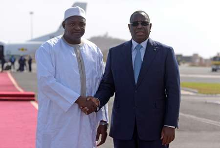 Senegal's President Macky Sall (R) shakes hands with the new President of Gambia Adama Barrow prior to leaving the Senegalese capital Dakar on January 26, 2017 ( SEYLLOU (AFP) )