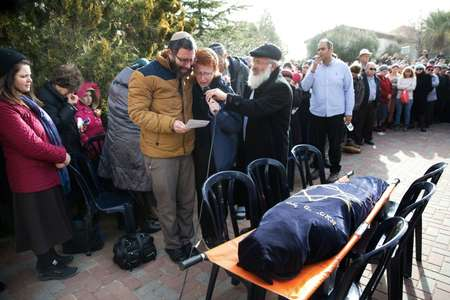 Natan, the husband of Dafna Meir, and her son speak during her funeral ceremony in the Jewish settlement of Otniel near the flashpoint city of Hebron in the southern West Bank on January 18, 2016 ( Menahem Kahana (AFP) )